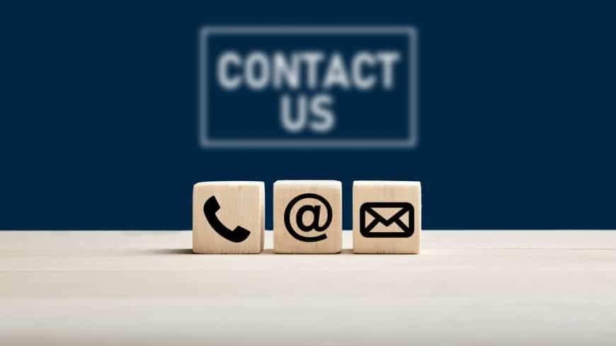 Phone and e-mail icons on wooden cubes with contact us text on blue background. Website page contact us or e-mail marketing concept.